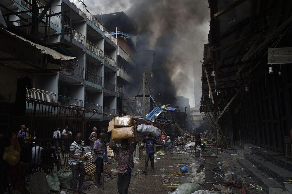 Lidé nosí zboží zachráněné před požárem v oblasti trhu Balogun v Lagosu