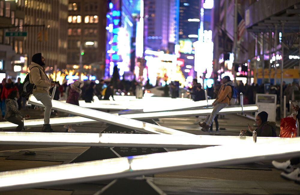 Lidé jezdí na zářících houpačkách na Broadwayi nedaleko Times Square v New Yorku