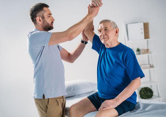 Terapeut dělá masáž staršímu pacientovi