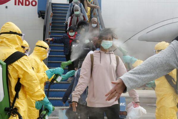 Lékaři stříkají indonéské občance antiseptikem po příletu z čínského Wu-chanu - Sputnik Česká republika