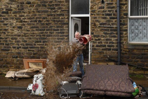 Muž uklízí dům po povodni, kterou přinesla bouře Ciara. Mytholmroyd , Velká Británie. - Sputnik Česká republika