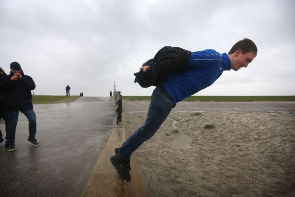 Muž na pobřežní hrázi během bouře Sabine v Nizozemsku - Sputnik Česká republika
