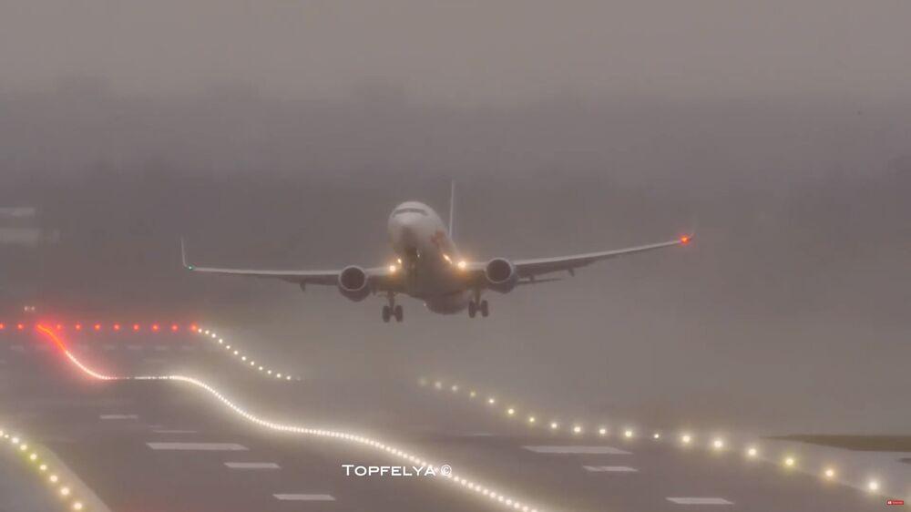 Letadlo přistává při složitých podmínkách během bouře Sabine. Letiště Birminghamu, Velká Británie.