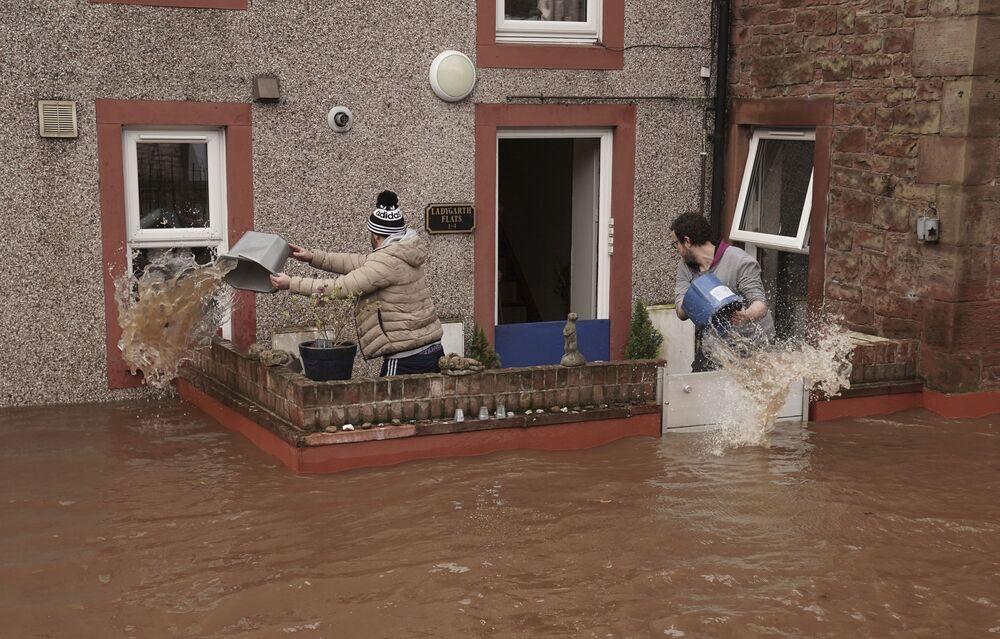 Muži nabírají vodu ze zatopeného domu. Appleby-in-Westmorland, Velká Británie.