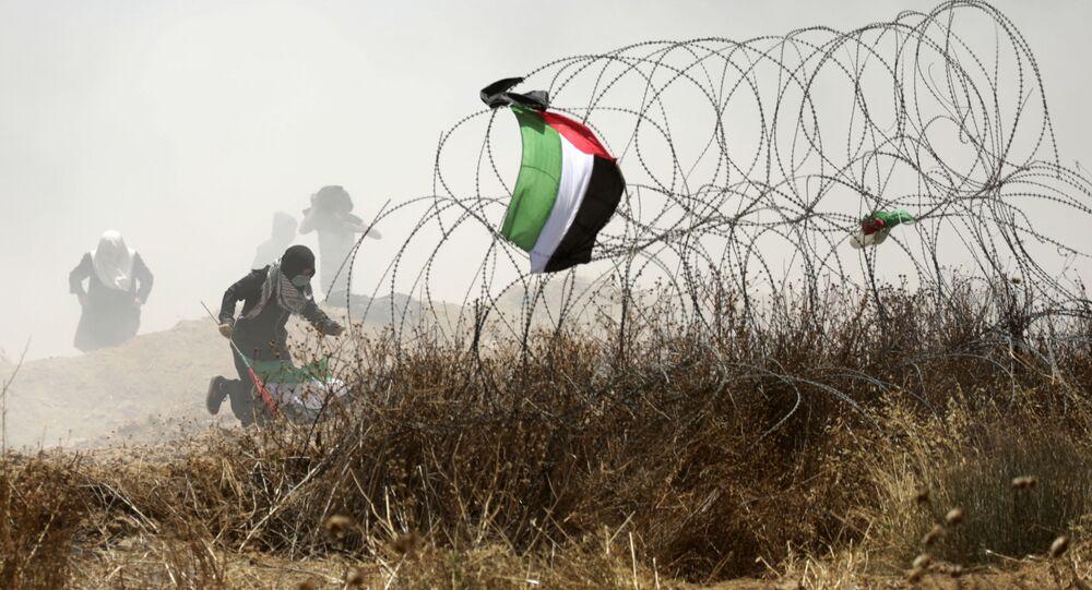 Palestinský protestujicí během střetu s izraelskými vojáky na hranici mezi Pásmem Gaza a Izraelem