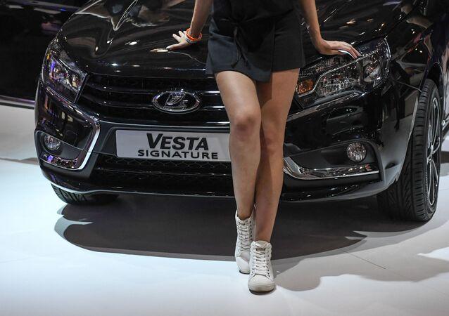 Modelka vedle automobilu značky LADA