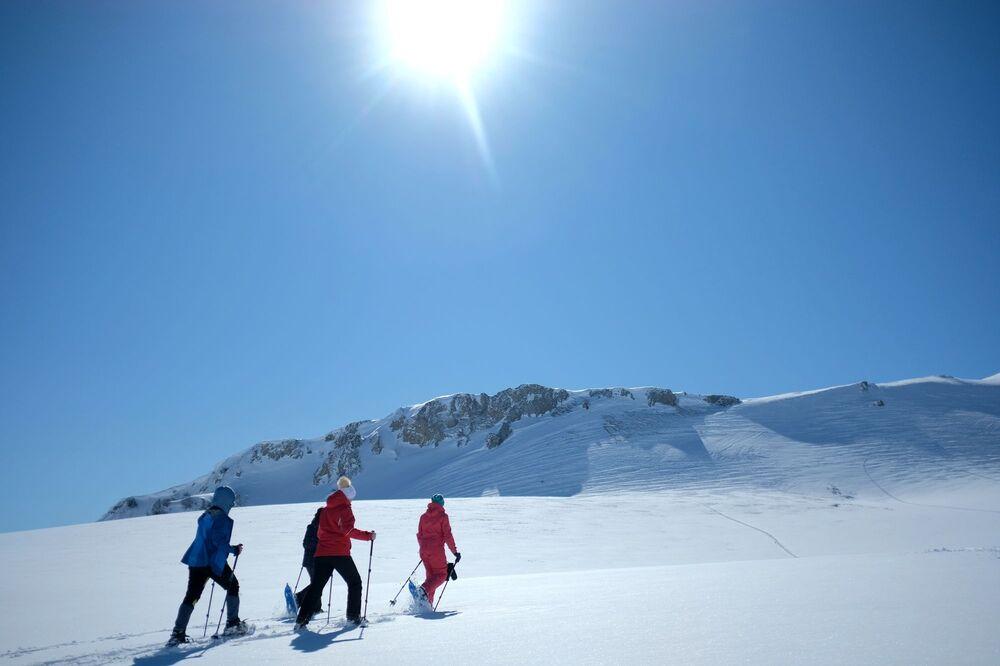 Turisté na sněžnicích na turistické trase podél náhorní plošiny Lago-Naki Kavkazské státní přírodní biosférické rezervace