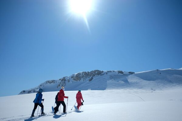 Turisté na sněžnicích na turistické trase podél náhorní plošiny Lago-Naki Kavkazské státní přírodní biosférické rezervace - Sputnik Česká republika
