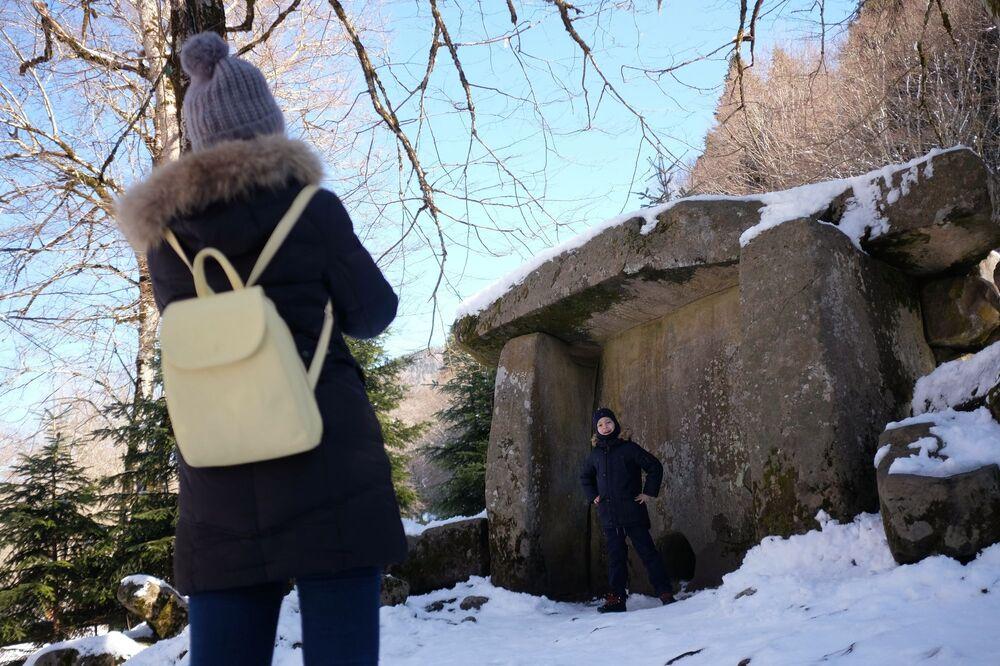 Turisté se fotografují v Guzerpilském dolmenu Kavkazské státní přírodní biosférické rezervace