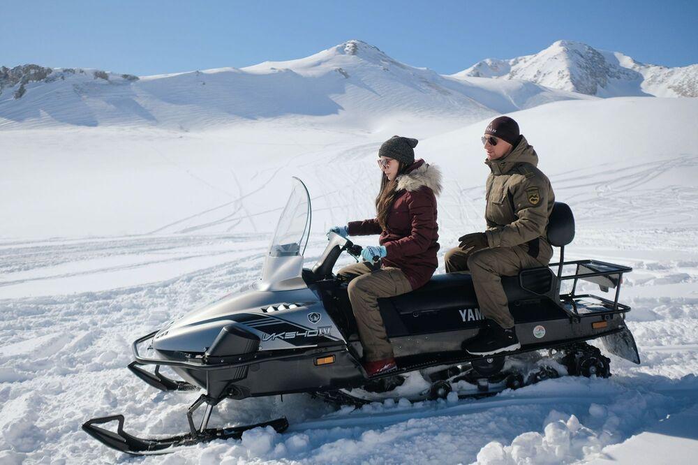 Turisté jezdí na sněžných skútrech na území náhorní plošiny Lago-Naki