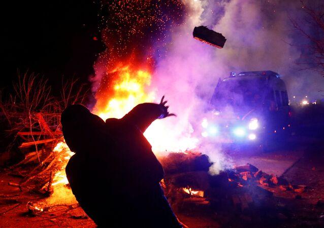 Protestující hází kameny na policejní vozidlo.