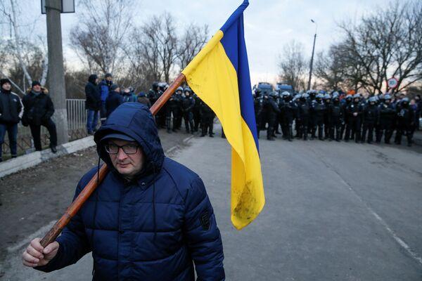 Muž drží ukrajinskou vlajku během protestní akce proti rozmístění evakuovaných občanů z Wu-Chanu v Poltavské oblasti. - Sputnik Česká republika