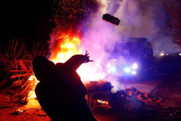 Protestující hází kameny na policejní vozidlo. - Sputnik Česká republika