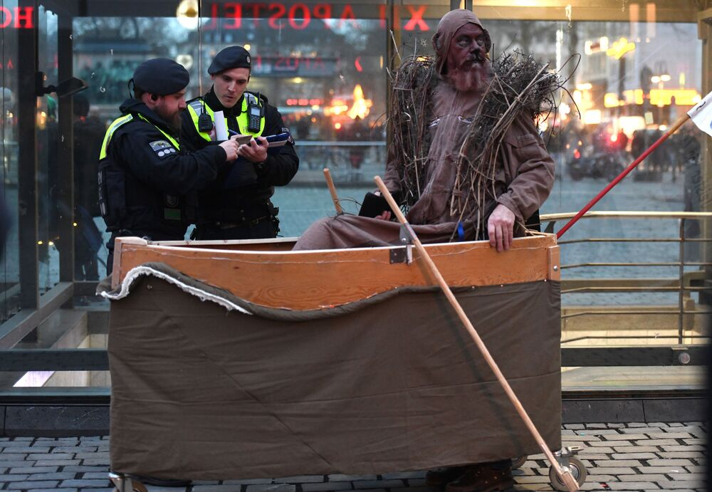 Policisté a protestující během demonstrace za zlepšení klimatu během karnevalového pochodu Geisterzug v Kolíně.