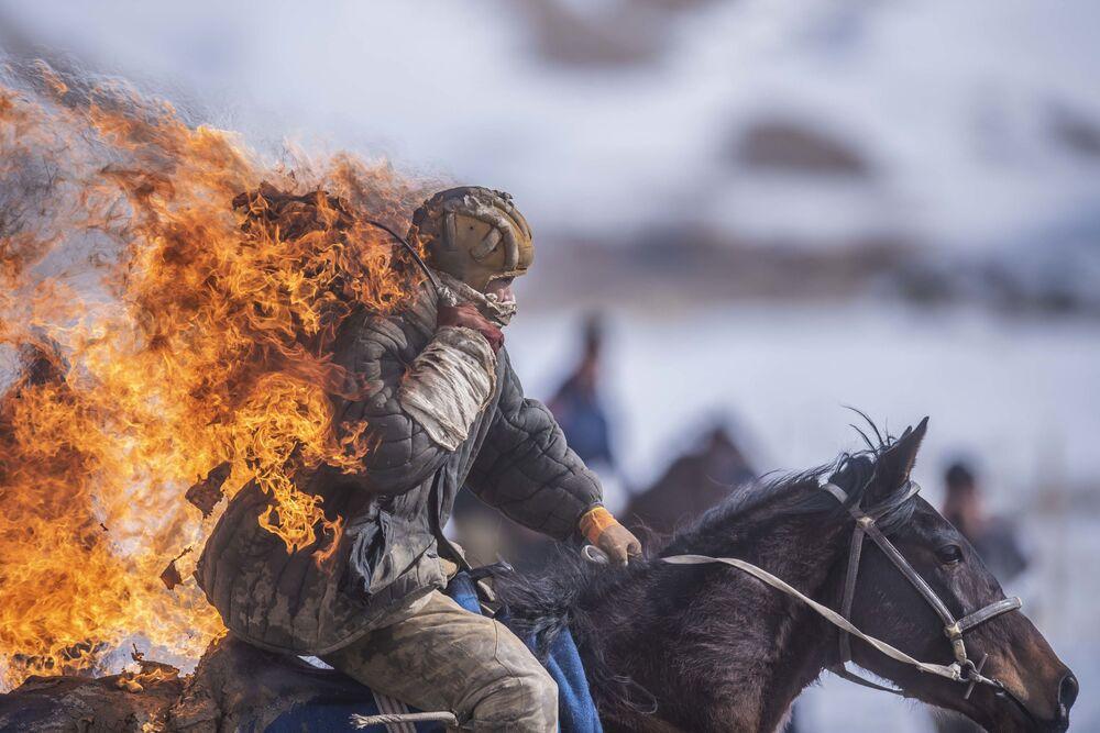 Kaskadér předvádí triky během ukázkové jízdy v rámci mistrovství v tradičním koňském sportu kok-boru v Kyrgyzstánu.