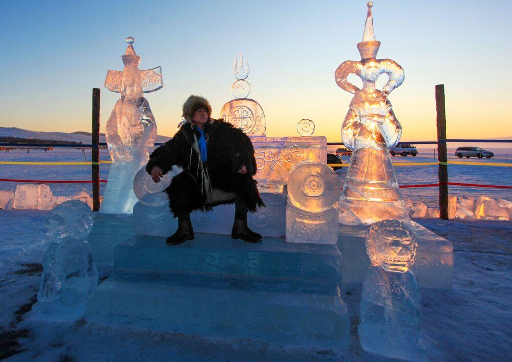 Muž sedí na ledovém trůnu, který byl představen na Mezinárodní soutěži ledových soch v rámci festivalu Olkhon Ice Fest u jezera Bajkal v Irkutské oblasti, Rusko