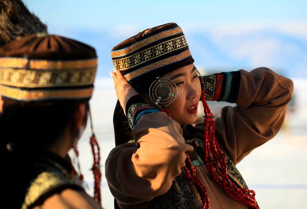 Ženy v tradičních oděvech na Mezinárodní soutěži ledových soch v rámci festivalu Olkhon Ice Fest u jezera Bajkal v Irkutské oblasti, Rusko