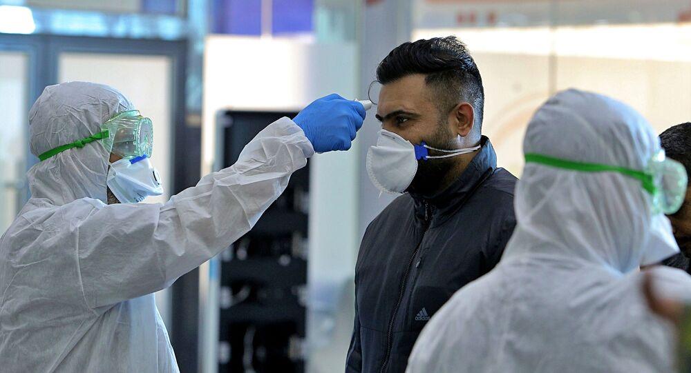 Zdravotnický personál na iráckém letišti Nadžaf kontroluje cestující, kteří přiletěli z Íránu