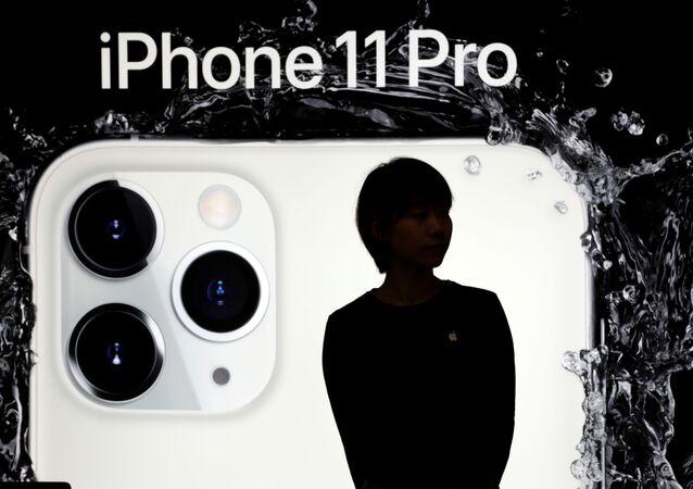 Žena na pozadí reklamy nového iPhone 11 Pro v Pekingu