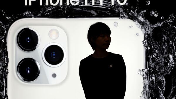 Žena na pozadí reklamy nového iPhone 11 Pro v Pekingu - Sputnik Česká republika