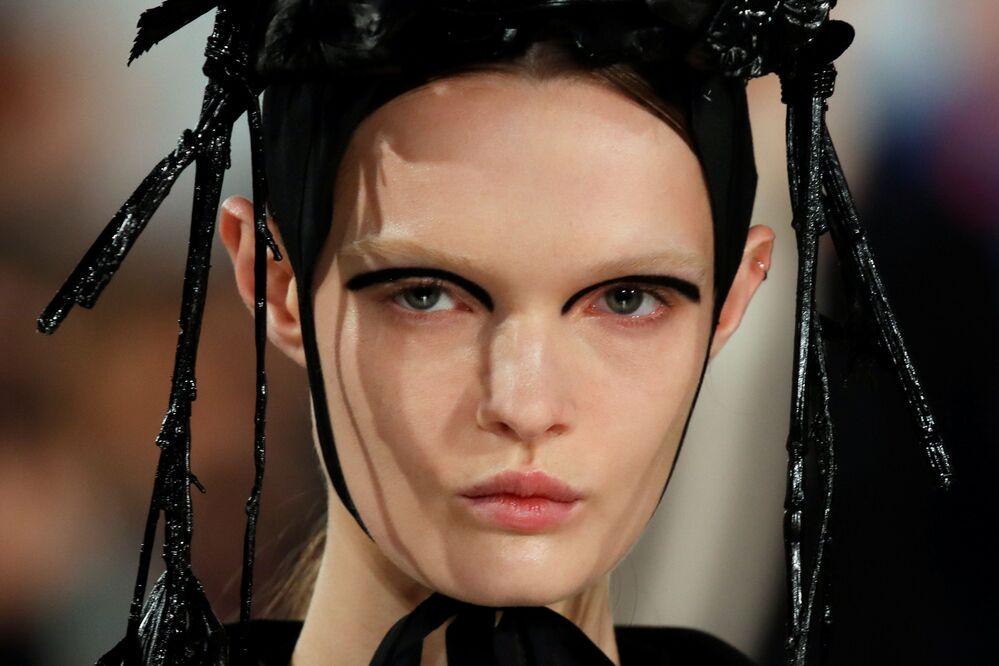 Modelka představuje tvorbu designéra Johna Galliana na pařížském týdnu módy