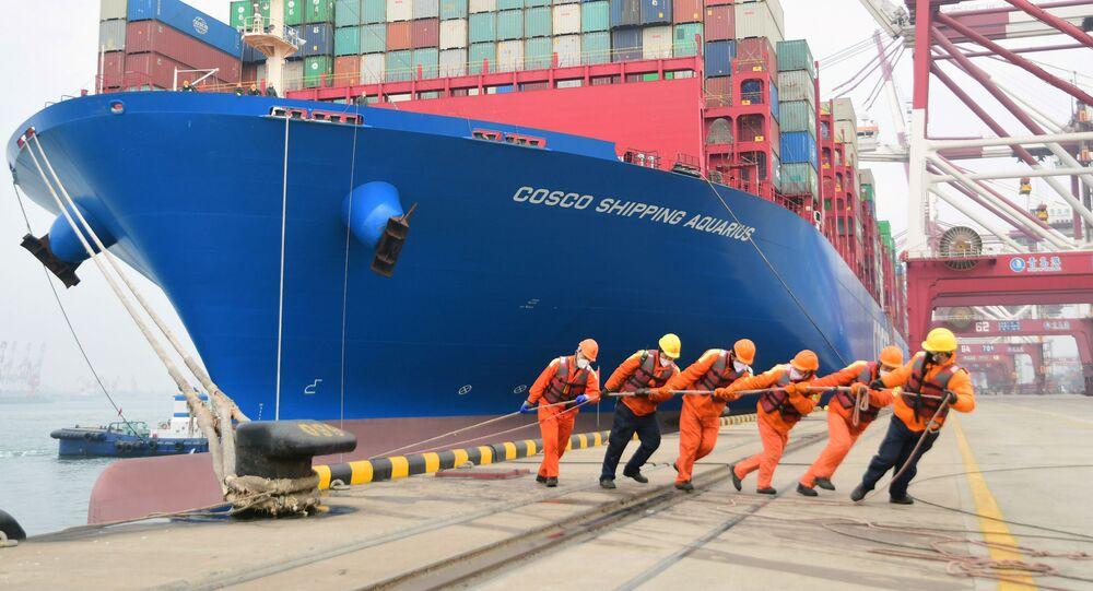 Pracovníci v rouškách přivazují loď v přístavu čínského města Čching-tao