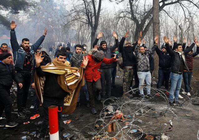 Migranti zvedají ruce na tureckém hraničním přechodu do Řecka Pazarkule.