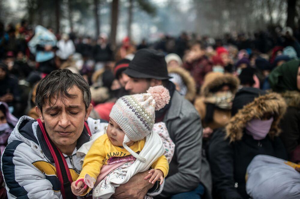 Žena drží dítě během střetů s řeckou policií na turecko-řeckém hraničním přechodu Pazarkule.