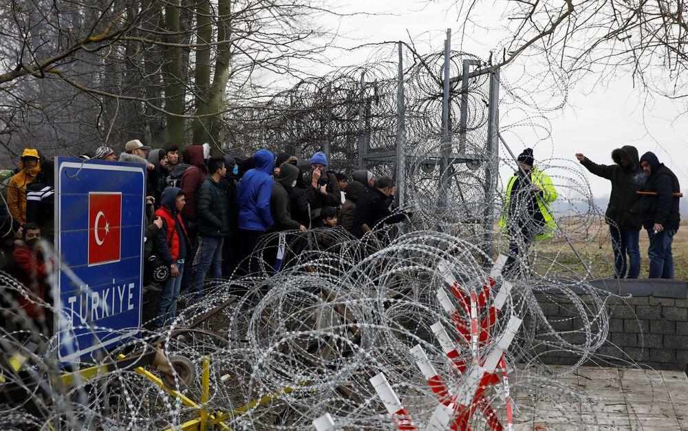 Muž mluví s řeckými policisty přes ostnatý drát na hranici mezi Tureckem a Řeckem.