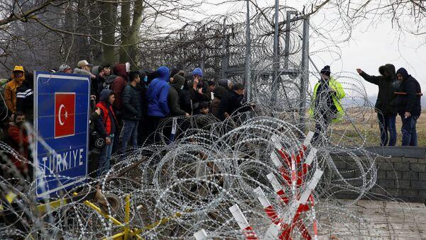 Muž mluví s řeckými policisty přes ostnatý drát na hranici mezi Tureckem a Řeckem - Sputnik Česká republika