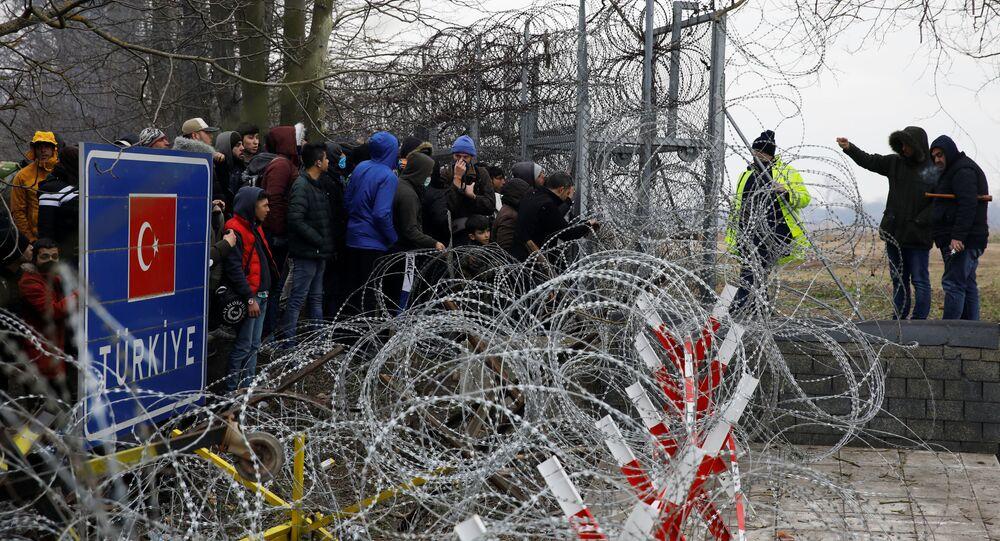 Muž mluví s řeckými policisty přes ostnatý drát na hranici mezi Tureckem a Řeckem