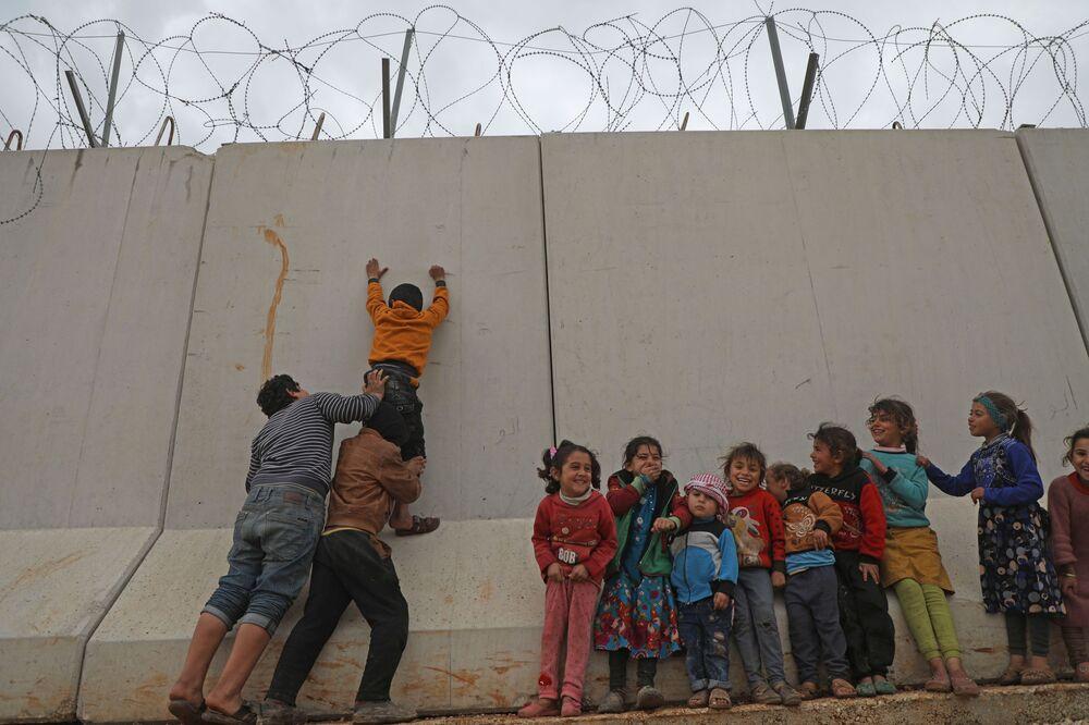 Syrské děti se snaží dostat se přes tureckou hraniční zeď na severozápadě Sýrie