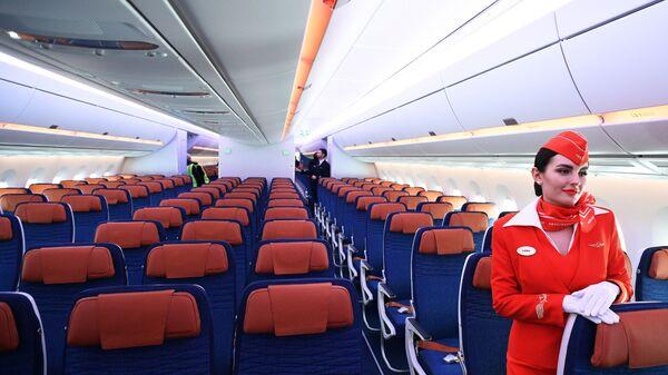 Стюардесса в салоне дальнемагистрального широкофюзеляжного пассажирского самолета Airbus A350-900 авиакомпании Аэрофлот - Sputnik Česká republika
