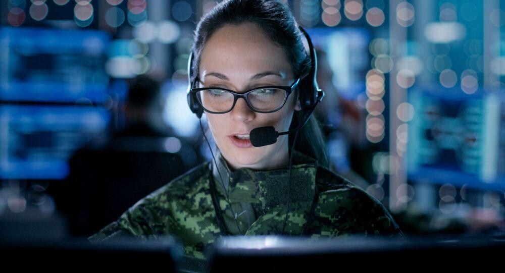 Dívka ve vojenské uniformě sedí za počítačem