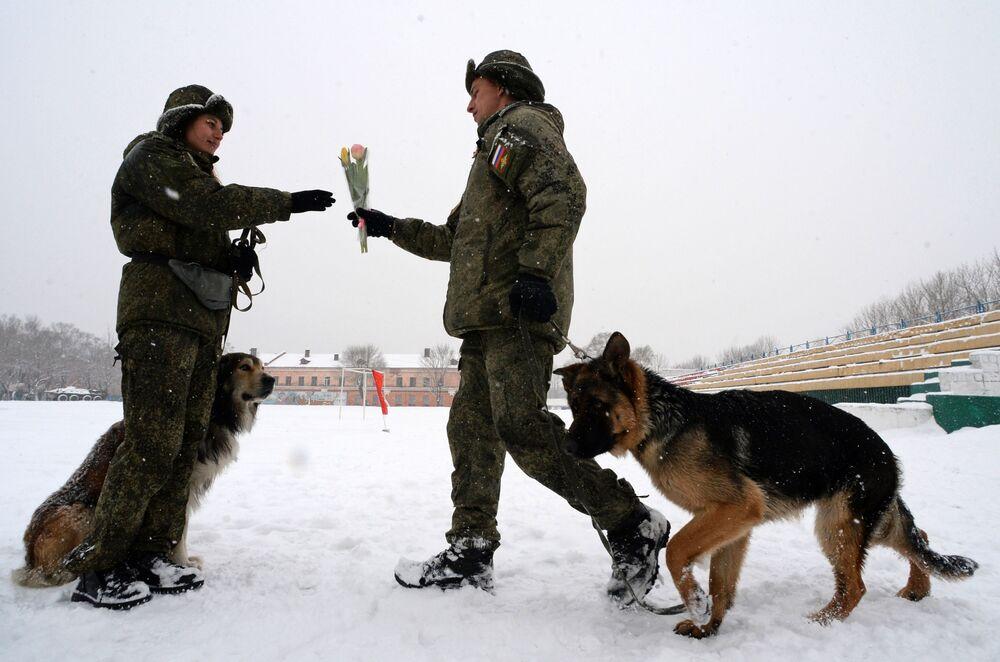 Kynolog blahopřeje své kolegyni k nadcházejícímu svátku 8. března. Soutěž vojenských kynologů Věrný přítel v Ussuriysku, Rusko.