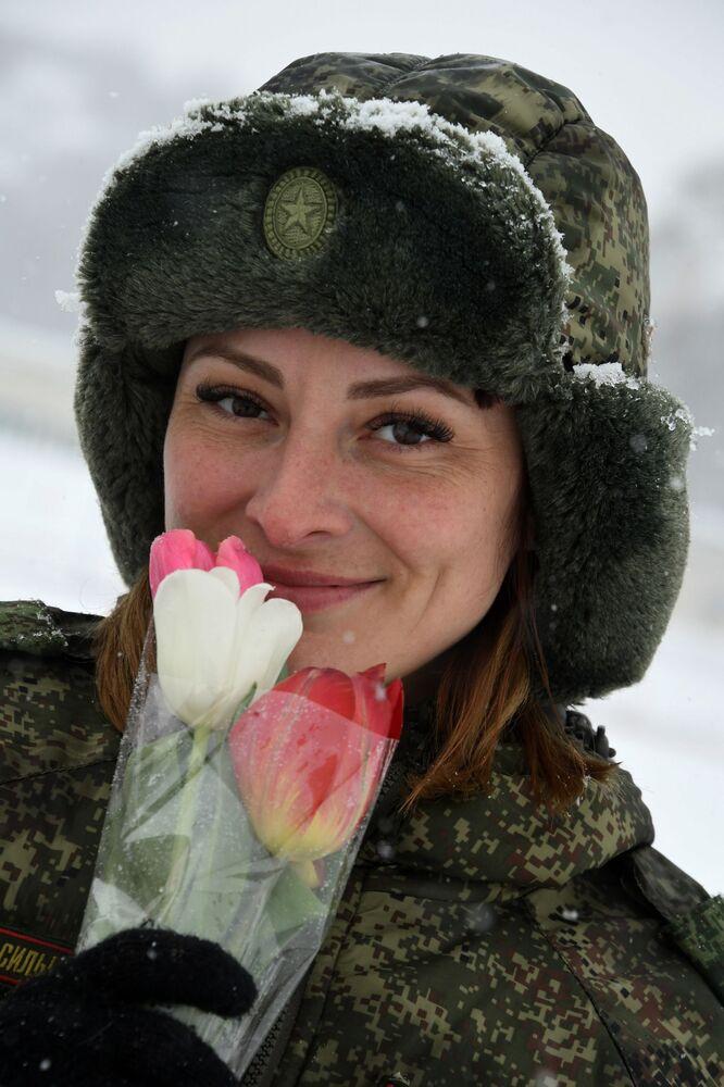 Kynoložka s květinami. Soutěž vojenských kynologů Věrný přítel v Ussurijsku, Rusko.
