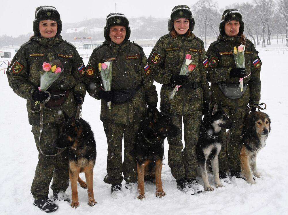 Kynoložky s květinami na počest nadcházejícího 8. března v Ussuriysku. Soutěž vojenských kynologů Věrný přítel v Ussurijsku, Rusko.