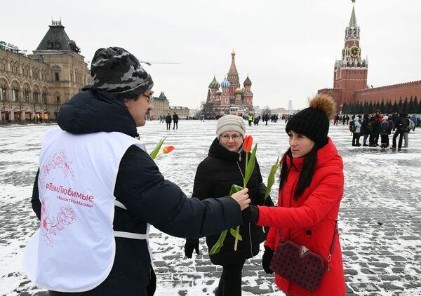 Dobrovolník dává ženám květiny a gratuluje k 8. Března.  - Sputnik Česká republika