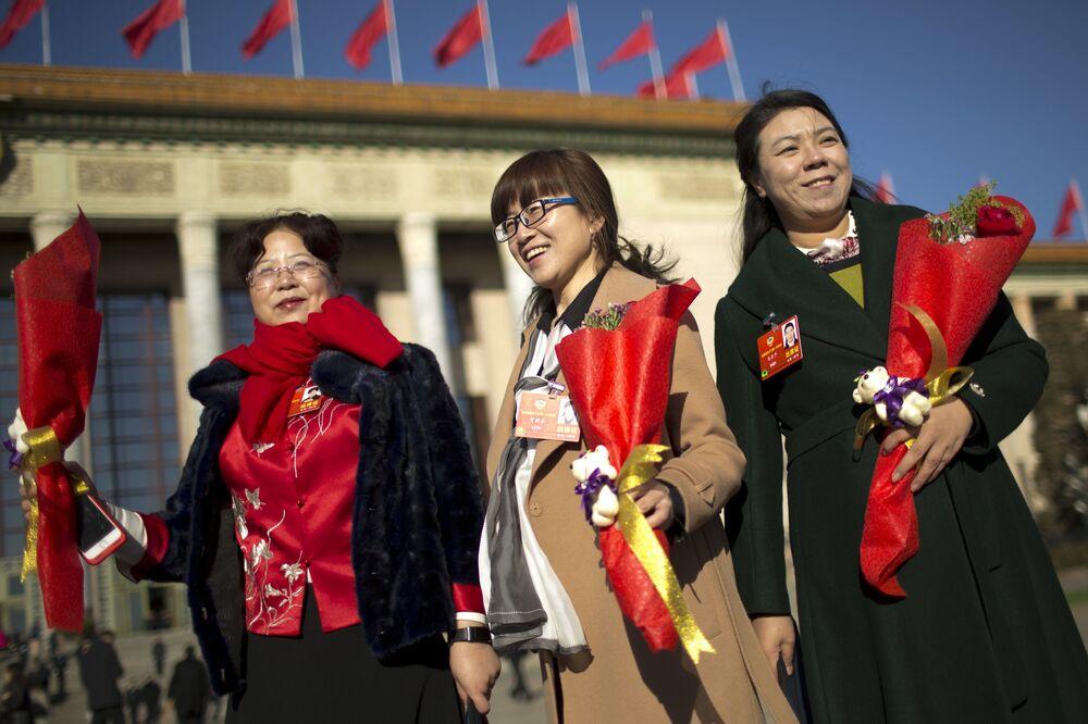 Delegátky s květinami poblíž Velkého sálu lidu v Pekingu během Mezinárodního dne žen