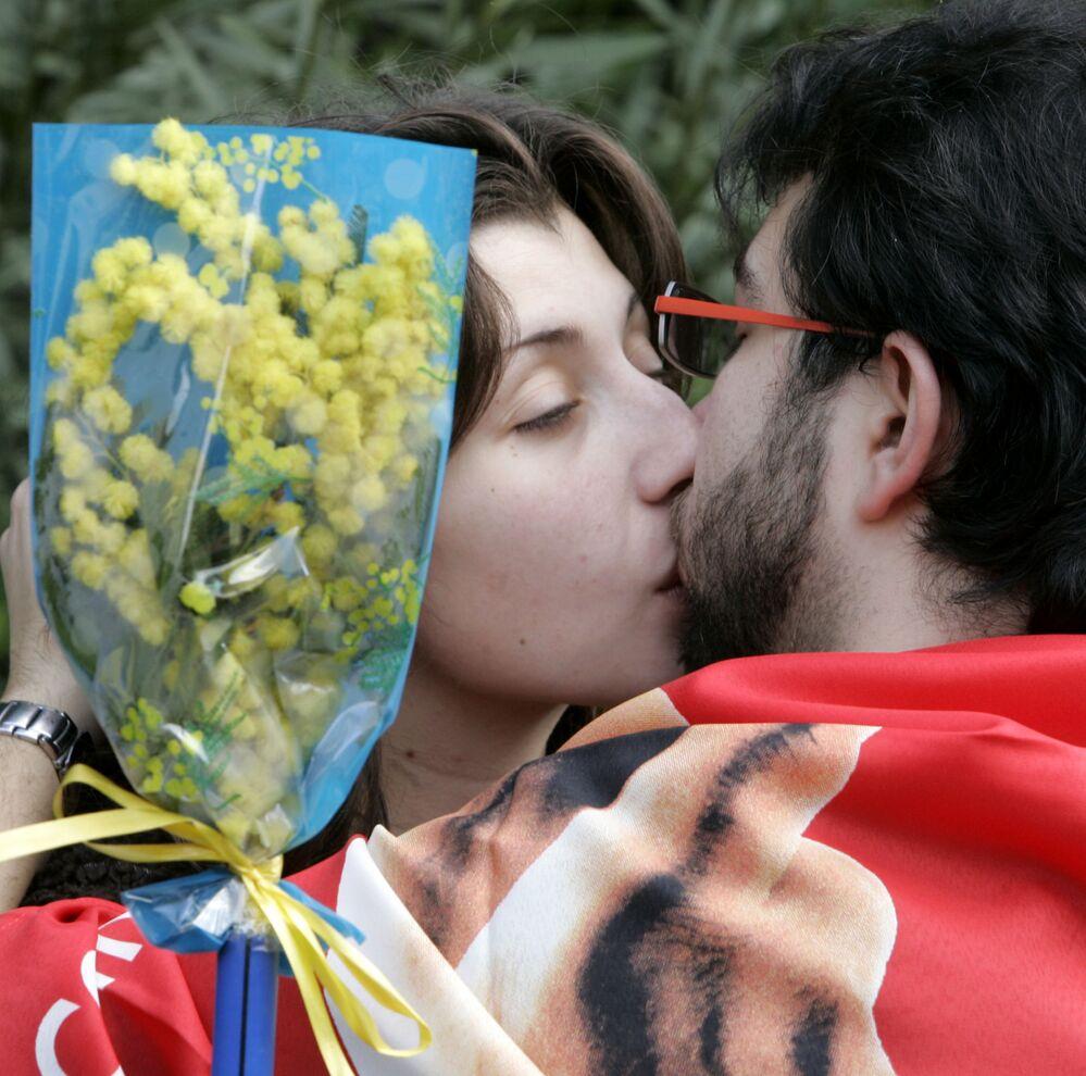 Pár se líbá během demonstrace na počest Mezinárodního dne žen. Řím, Itálie