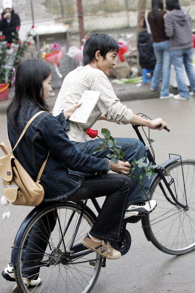 Dívka s růží na kole. Hanoj, Vietnam