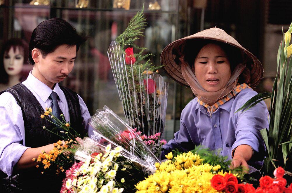 Mladý muž kupuje růže ve staré čtvrti Hanoje, Vietnam