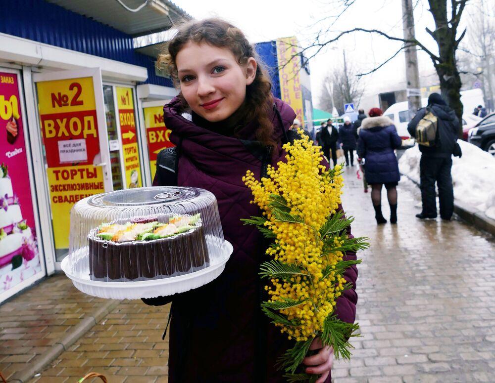 Obyvatelka Doněcku s kyticí mimózy a dortem na Mezinárodní den žen