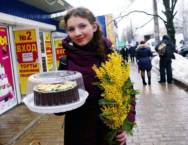 Obyvatelka Doněcku s kyticí mimózy a dortem na Mezinárodní den žen - Sputnik Česká republika