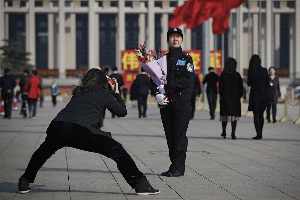 Žena fotí policistku 8. března v Pekingu