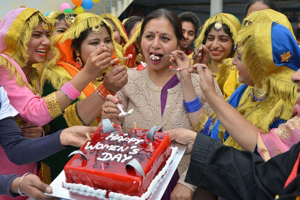 Studentky vysoké školy pohošťují dortem svou ředitelku. Mezinárodní den žen v Amritsaru, Indie