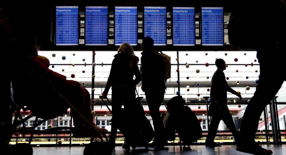 Cestující před tabulkou na letišti. Illustrační foto