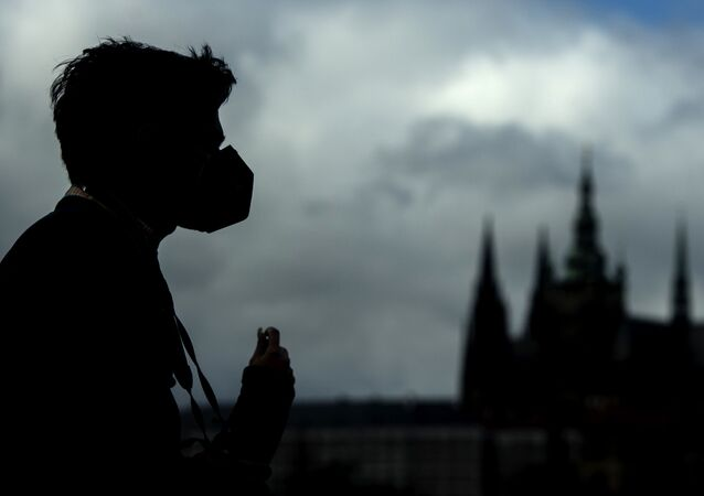Silueta muže v roušce na Karlově mostě v Praze