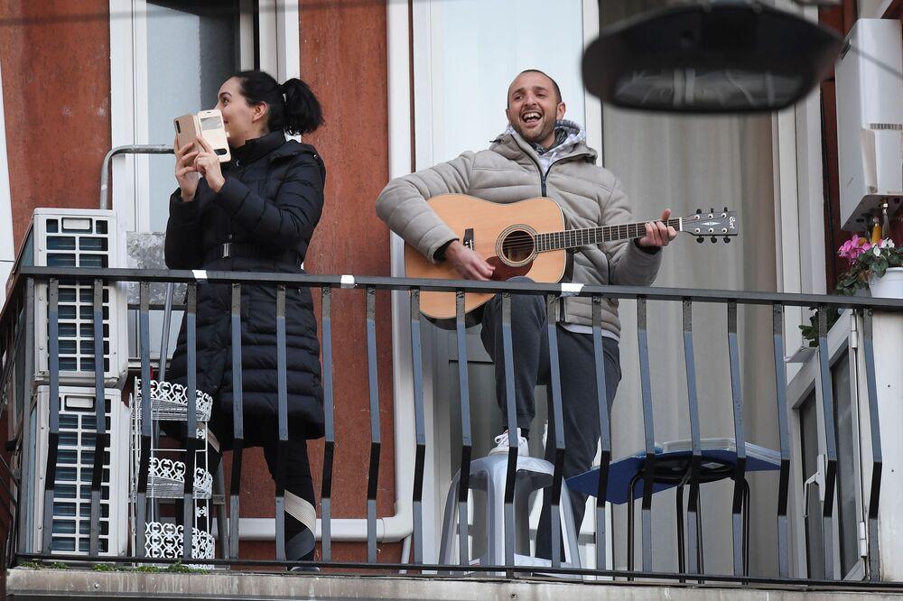 Muž s kytarou a žena s telefonem na balkóně v Miláně