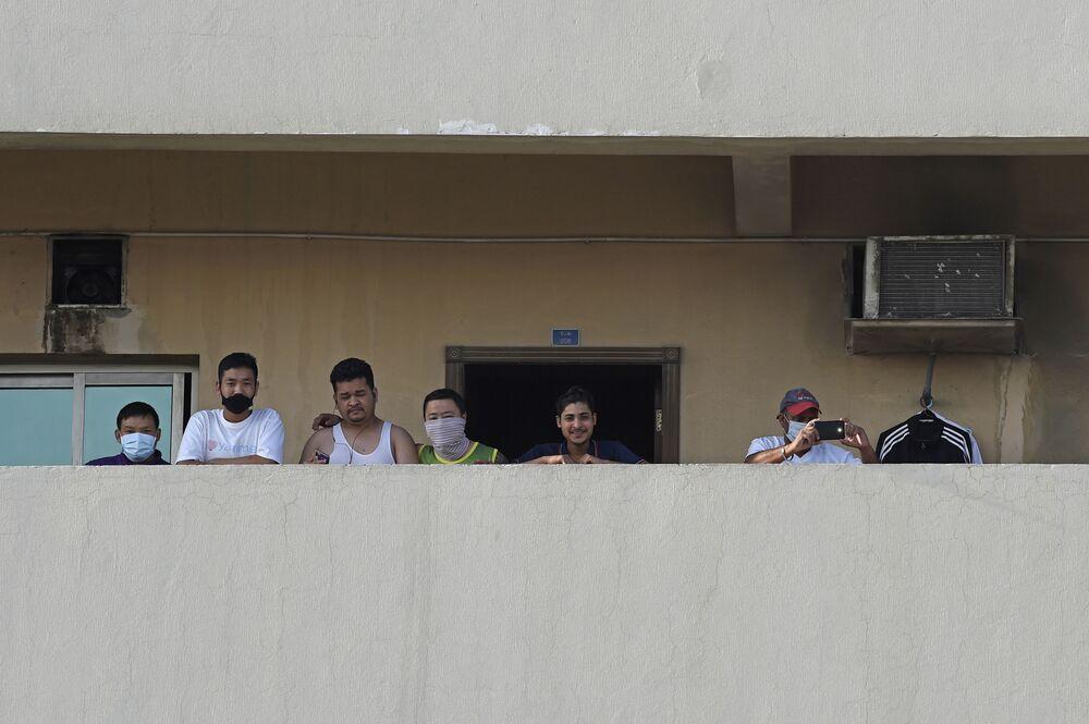 Dělníci na balkóně domu ve městě Manáma, Bahrajn